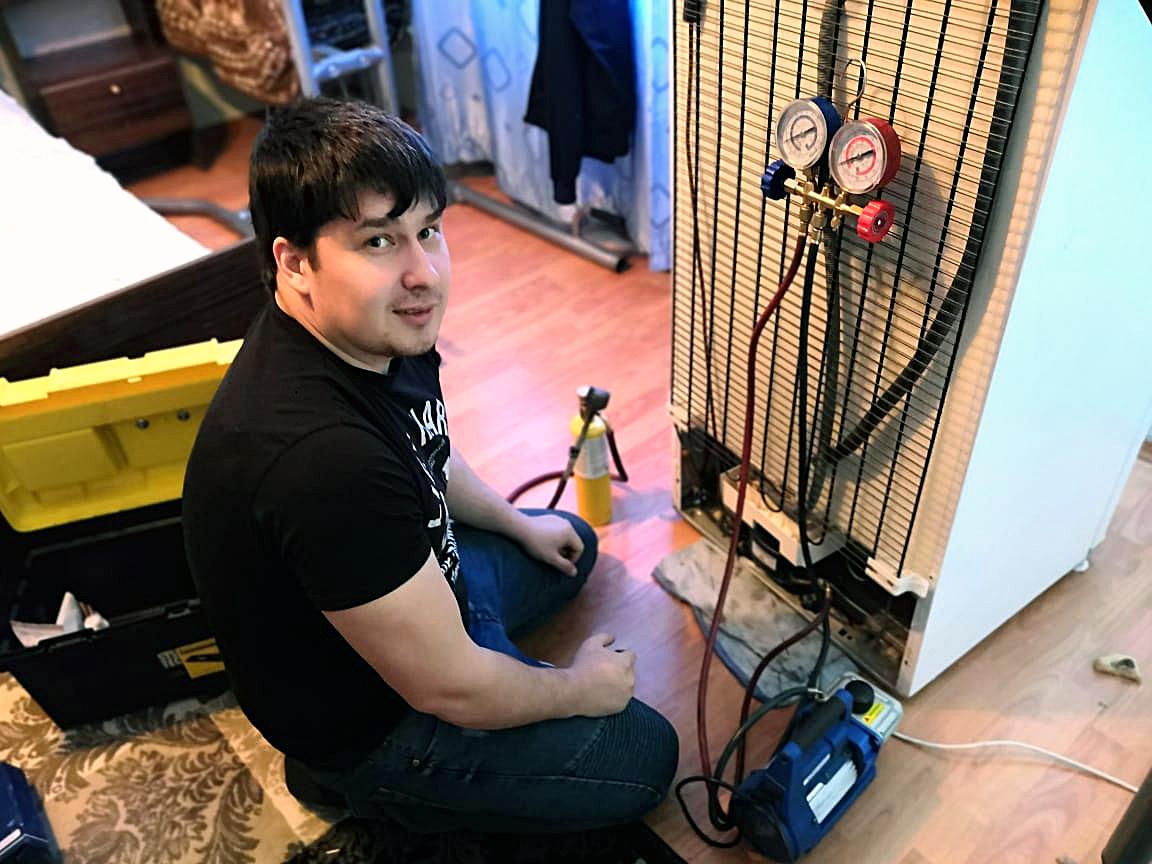 Специалист Денис Дегтярев в процессе ремонта холодильника